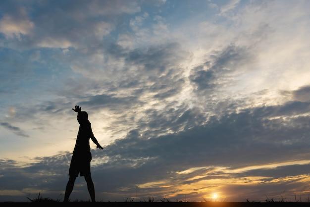 Silhouette d'un homme avec un homme exerçant au coucher du soleil.
