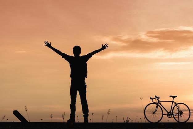 Silhouette de l'homme a levé les mains avec le vélo sur la route au coucher du soleil