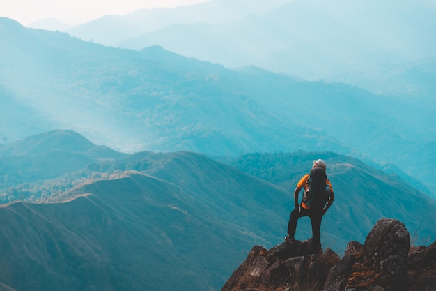 Silhouette d'homme lever la main sur le sommet de la montagne, concept de réussite