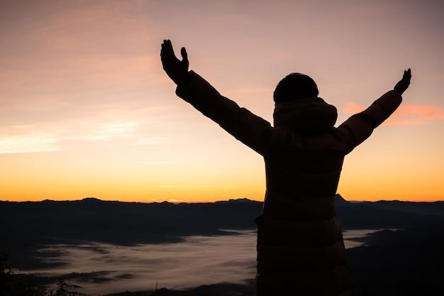 Silhouette d'un homme avec les mains levées au coucher du soleil.