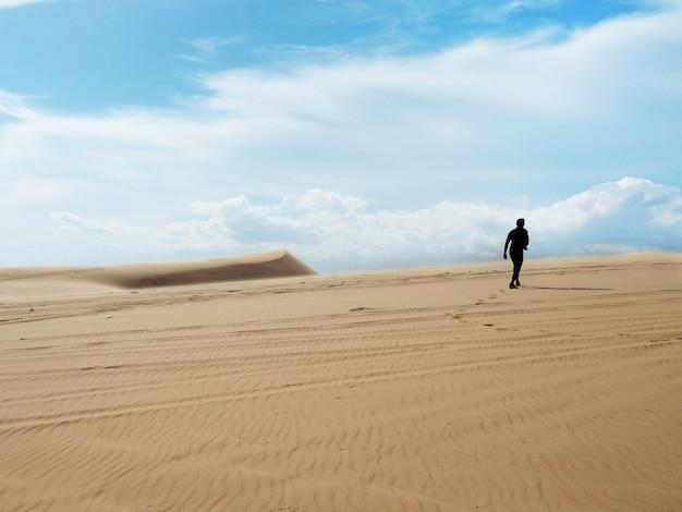 Silhouette d'un homme marchant sur une dune de sable.