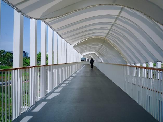 Silhouette d'homme marchant sous un tunnel blanc