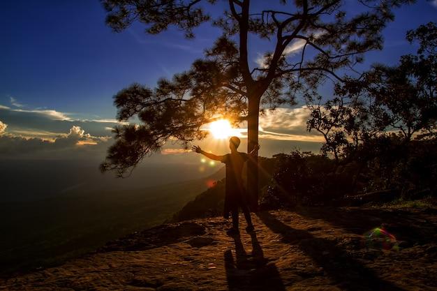 Silhouette de l'homme montrent bras pour les réalisations réussies et célébrant le succès sur le coucher du soleil et silh