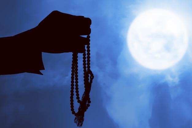 Silhouette d'homme musulman priant avec des perles de prière sur ses mains