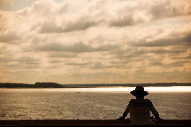 Silhouette d'un homme pêchant sur le pont. contexte.
