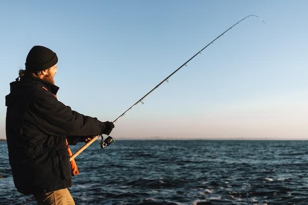 Silhouette d'homme pêcheur portant un manteau, tenant une tige, pêchant à la plage