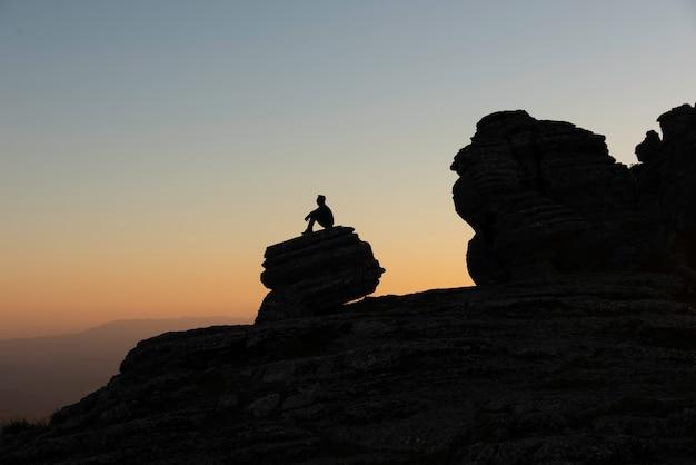 Silhouette d'homme sur des pierres regardant l'horizon alors qu'il fait noir