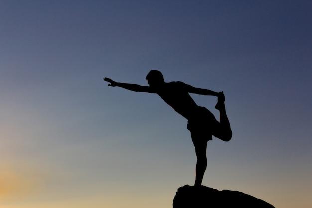 Silhouette d'homme pratiquant le yoga au coucher du soleil sur un rocher dans la nature. rétro-éclairage. espace de copie.