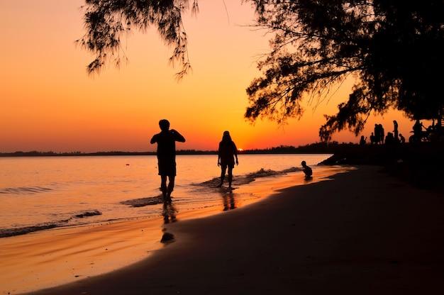 Silhouette d'un homme prenant une photo de sa petite amie sur la plage au coucher du soleil