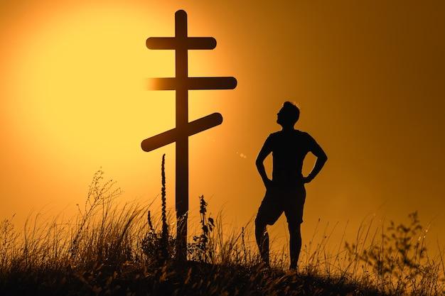 Silhouette d'homme près de croix orthodoxe au coucher du soleil.