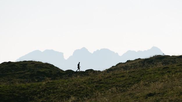 Silhouette d'un homme qui pratique la marche nordique dans les montagnes