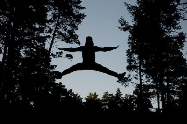 Silhouette homme sautant contre le ciel bleu.