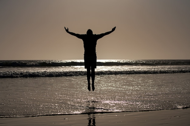 Silhouette d'homme sautant sur la plage. vue imprenable sur la plage au coucher du soleil.