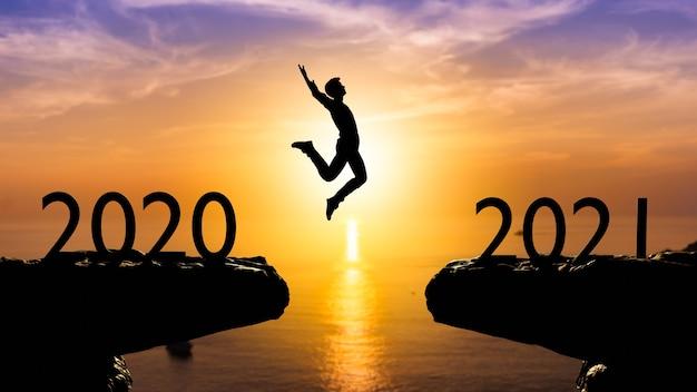 Silhouette homme saute entre 2020 et 2021 ans avec mur de coucher de soleil, concept de l'année 2021