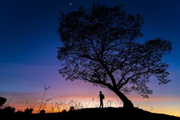 Silhouette un homme seul et un arbre pendant le coucher du soleil