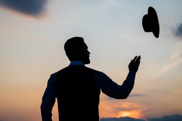 Silhouette d'homme en train de lever son chapeau sur le ciel du lever du soleil, insouciant.