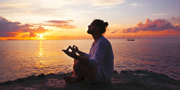 Silhouette d'homme d'yoga au fond du coucher du soleil.