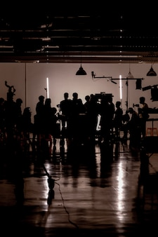 Silhouette des images de la production vidéo dans les coulisses, l'équipe lightman et le caméraman travaillant avec le réalisateur dans le studio