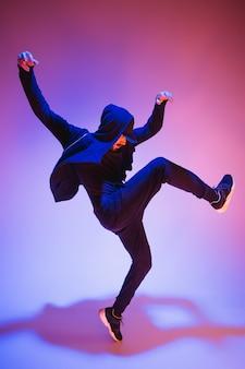 La silhouette d'un jeune danseur de break hip hop masculin dansant sur fond coloré
