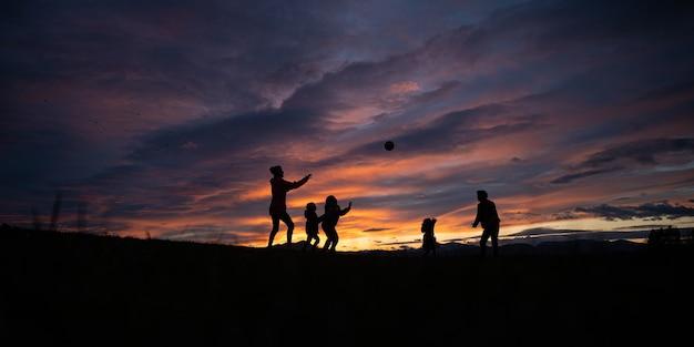 Silhouette d'une jeune famille de cinq personnes jouant avec un ballon à l'extérieur sous un beau ciel dramatique au coucher du soleil.