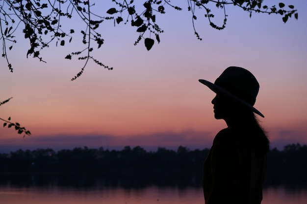 Silhouette d'une jeune femme contre la belle couleur pourpre du ciel du soir