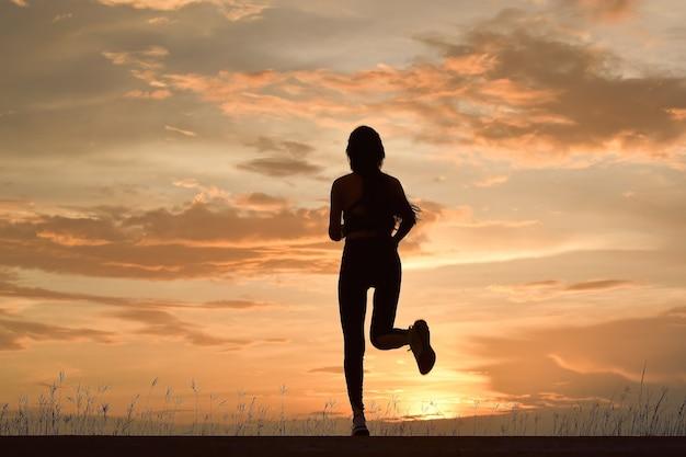 Silhouette de jeune femme en cours d'exécution. jeune femme sportive qui court sur route dans une nature magnifique.