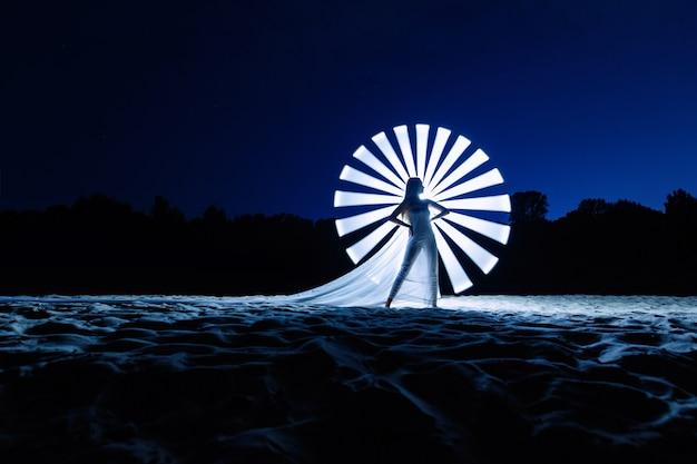 Silhouette de jeune femme dans la soirée avec ligne de lumière