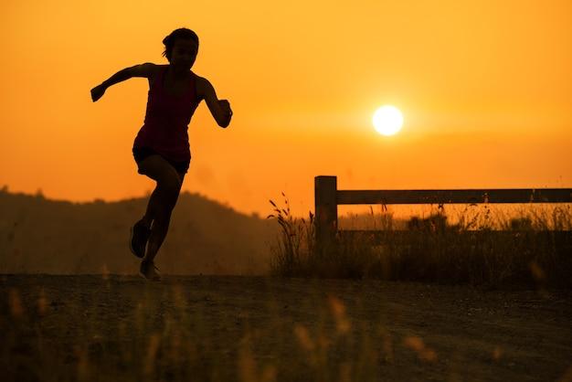 Silhouette jeune femme fitness en cours d'exécution heure du coucher du soleil