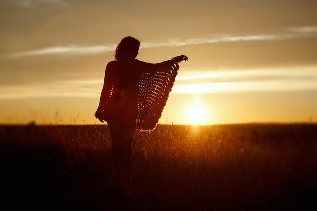 Silhouette de jeune femme heureuse au coucher du soleil, fille en plein air dans un poncho à carreaux dans un champ avec des épillets