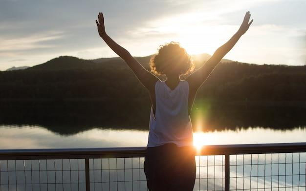 Silhouette d'une jeune femme libre et heureuse avec la soleil vivant de coucher de soleil sur un lac