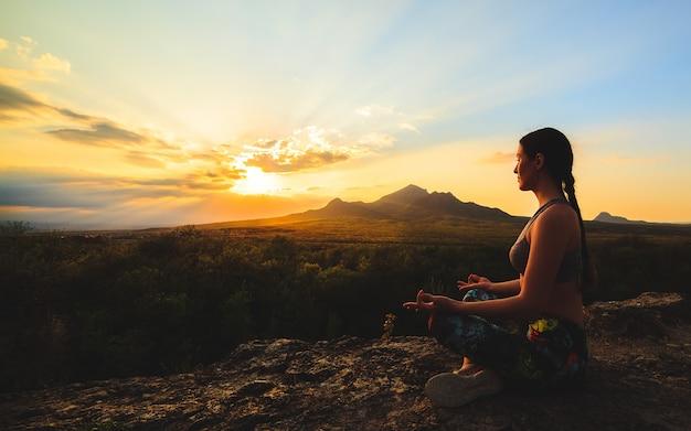 Silhouette de jeune femme pratiquant le yoga au coucher du soleil