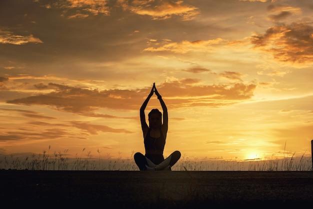 Silhouette jeune femme pratiquant le yoga méditation sur la plage au coucher du soleil