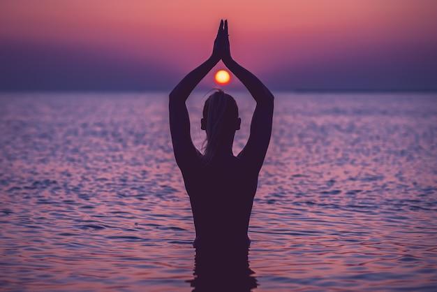 Silhouette de jeune femme pratiquant le yoga sur la plage au lever du soleil
