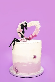 Silhouette de jeune femme s'asseoir sur un gâteau à la crème avec coeur en cristaux