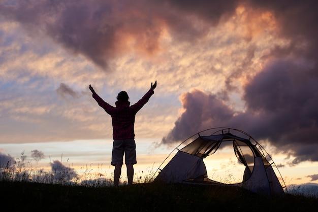 Silhouette de jeune femme avec ses mains en appréciant le beau ciel du soir près de tente au sommet d'une colline de montagne. nuit soirée touriste grimpeur majestueux incroyable vue paysage