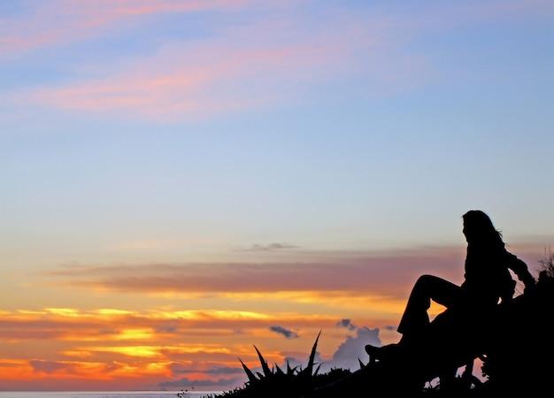 Silhouette de jeune fille assise sur une bûche d'arbre, regardant la magnifique plage de coucher du soleil.