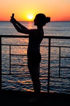 Silhouette d'une jeune fille au coucher du soleil crépuscule, vagues. fille maki