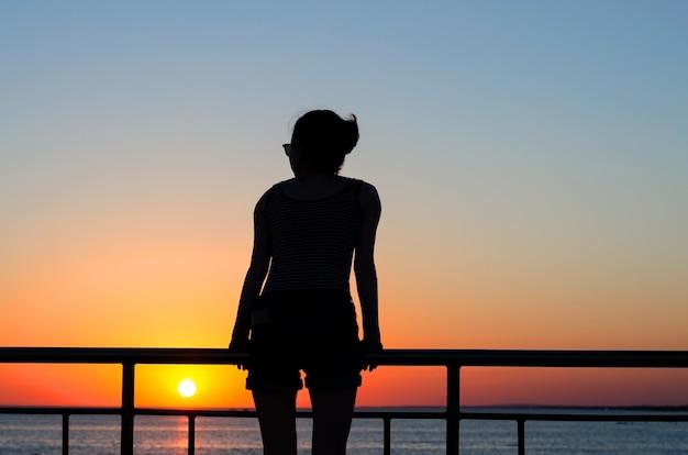 Silhouette d'une jeune fille au coucher du soleil crépuscule, vagues. la fille