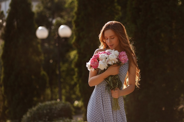 Silhouette d'une jeune fille au coucher du soleil. dans ses mains un bouquet de fleurs d'été