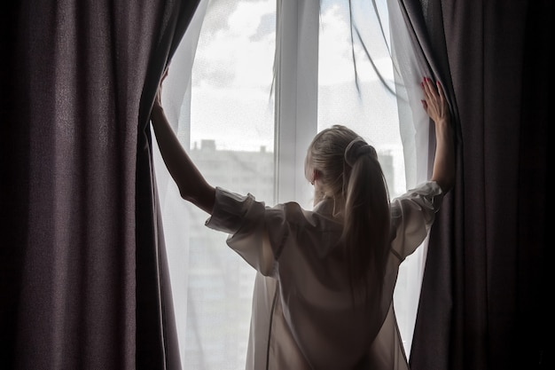 Silhouette de jeune fille en chemise d'hommes blancs à la fenêtre. vue arrière.