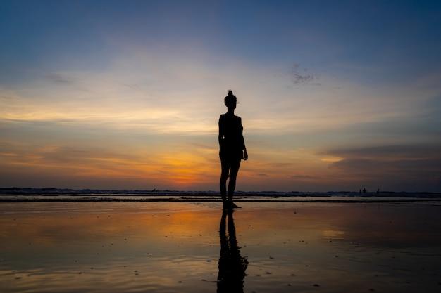 Silhouette d'une jeune fille debout dans l'eau sur une plage au coucher du soleil