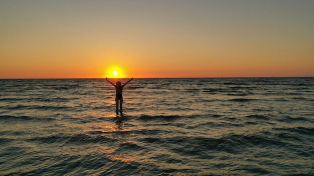 Silhouette d'une jeune fille détendue en maillot de bain dans la mer au lever du soleil. bonnes vacances vacances concept.