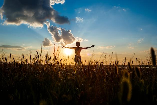 Silhouette de jeune fille sportive, pratiquer le yoga dans le champ au lever du soleil.