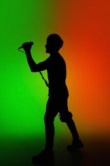 Silhouette de jeune guitariste masculin caucasien isolé sur un studio dégradé bleu-rose à la lumière du néon