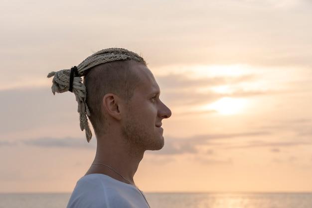 Silhouette d'un jeune homme avec des dreadlocks sur la tête près de la mer pendant le coucher du soleil. portrait en gros plan. heureux bel homme avec des dreadlocks sur la plage tropicale