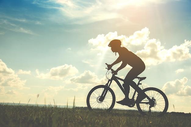 Silhouette jeune homme du cyclisme sur fond de coucher de soleil
