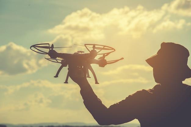 Silhouette d'un jeune homme jouant avec le drone au coucher du soleil