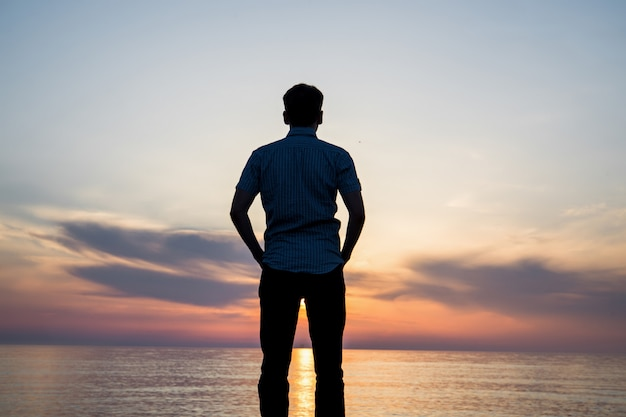 Silhouette de jeune homme sur la plage au coucher du soleil