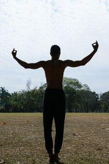 Silhouette d'un jeune homme torse nu brésilien avec le dos et les bras ouverts dans un parc public.