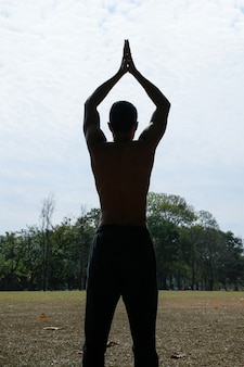 Silhouette de jeune homme torse nu brésilien, le dos tourné et les mains au-dessus de sa tête.